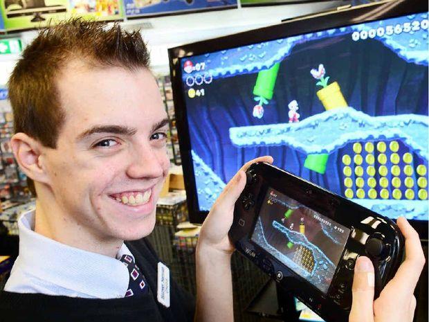 BIG STEP UP: Harvey Norman Ipswich salesman Chris Malone test drives the Wii U.