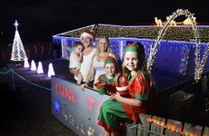 Madison Lake, 7, with her brother Kybe, 8, dressed as Christmas elves pose outside their family home that is adorned with Christmas lights. Parents Rebecca Miles and Brady Gray hold baby Dexton Gray, 2. Mr Gray has programmed the Christmas lights to flash in time with six songs including Gangnam Style. Photo: Claudia Baxter / The Queensland Times