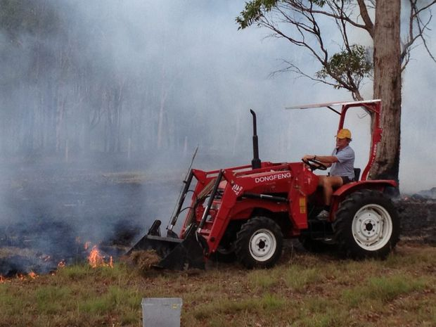 Local resident Trevor Davidson uses his tractor to help fight the fire at Sunshine Acres.