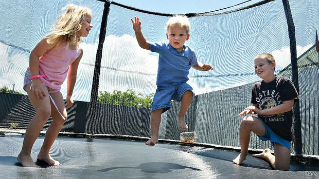 SAFE FUN: Ella Sleeman, Mason Willoughby (centre) and Jordan Sleeman bounce safely on their trampoline yesterday. CHOICE is warning parents to check trampoline safety.