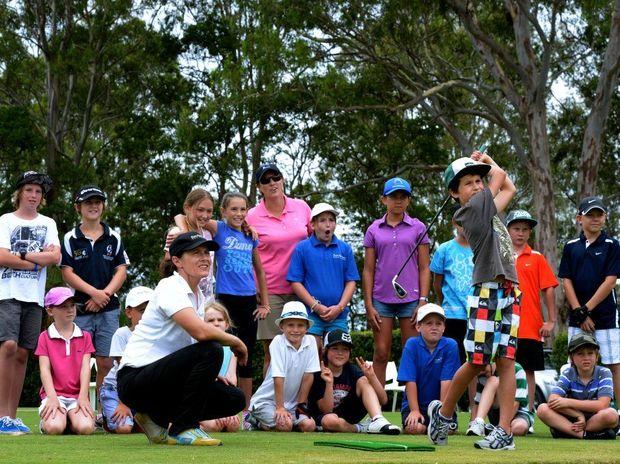 Rachel Hetherington works with 9 yo Jimmy Bourne at the kids golf clinic at Rachel Hetherington driving range. Photo: John Gass / Daily News