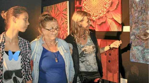 LOVING THE ART: Kayona Mudita and her mother Patrizia, visitors from overseas, enjoy some of the paintings in the Community Centre, with Pippy Wardell of Byron Bay (centre).