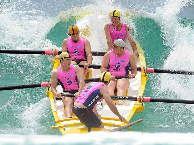 The Yamba Reserve crew gets buffeted by a wave as they head out during a recent event. PHOTO: CONTRIBUTED