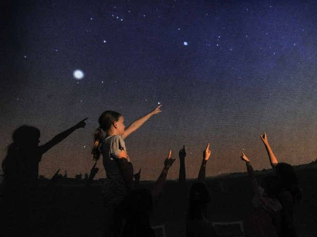 ANOTHER WORLD: Emily Bloomfield, 10, points to the stars with her friends at the Lismore Art Gallery to see the StarLab Cosmodome Show.