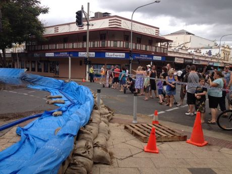 A crowd gathers in the Marybrough CBD to see the floodwaters.
