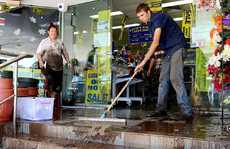 STEP TO IT: The community band together to clean Laidley's Wayne's World shop. The water reached about 20cm above the 2011 flood mark.