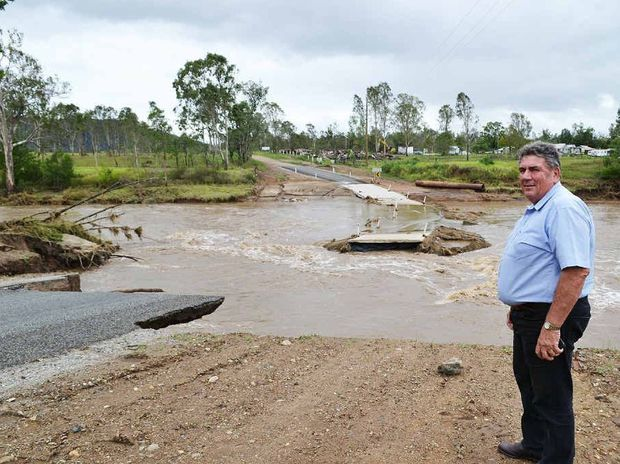 OBLITERATED: Mayor Graeme Lehmann inspects the damage at Ivory Creek Rd in Toogoolawah.
