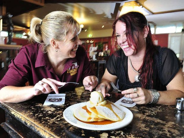 GIVING A TOSS: Pancake Manor Ipswich manager Joanne Harbort (left) and Ipswich Women's Shelter support worker Michelle tuck into lunch.