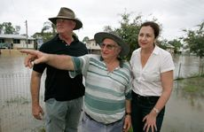 Depot Hill resident Wayne Wisley (centre) points to where the flood waters came up to in 2010 as L-R local member Bill Byrne and opposition leader Annastacia Palaszczuk look on as the Fitzroy River rises past 8.2 to an estimated 8.5 peak at Rockhampton. Photo: Chris Ison / The Morning Bulletin
