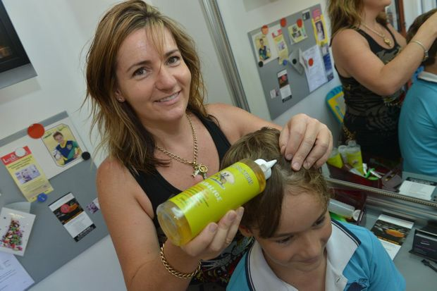 Janine Heard of Lice Doctors checks Matson Heard's (9) hair for lice. Photo: John McCutcheon / Sunshine Coast Daily