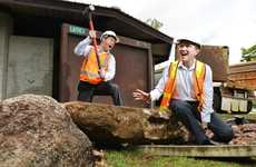 Crs Andrew Antoniolli and David Morrison act up during the demolition of the public amenities block in Queens Park. A new block will be built on the site as part of the park revamp.