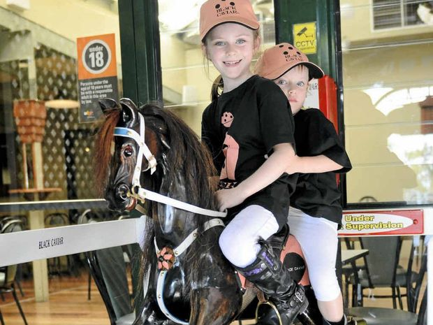 THE FAVOURITE: Hand carved by Greg Ryan from local silky oak timber, this rocking horse named Black Caviar was ridden by local girls Shani and Elsie Firth at Roche's Hotel.Photo Debrah Novak