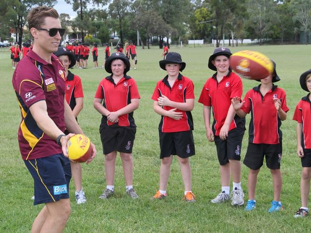 James Polkinghorne teaching kids about Aussie rules at Our Lady of the Southern College on Friday.