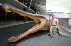Australia Zoo artist Cameron Chapman with his latest work, the 13 metre long, 5.3 tonne Sarcosuchus imperator.
