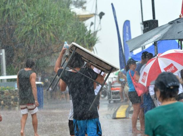 Crowds take shelter from heavy rain at the Ironman event in Noosa.