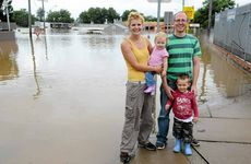 Gemma and Nick Green of PC Place, with their children Evie and Sidney, watch from a distance as the flood falls below the ceiling of their business premises on River Rd.