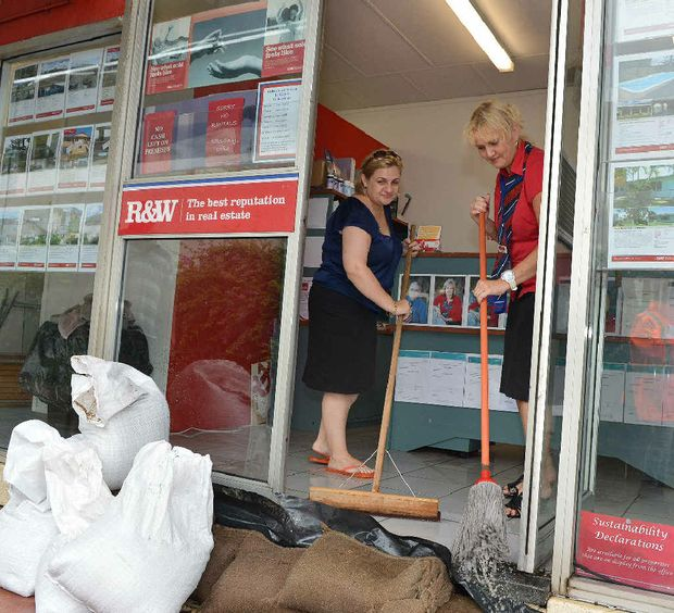 Jaci Foster and Toni Calcutt, of R&W; Real Estate, mop up their Nebo Rd office after heavy rain.