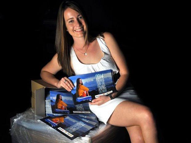 CALENDAR GIRL: Jupiters Summer Surf Girl entrant Emily Prain promotes the new 2014 Bundaberg Surf Life Saving Club fundraising calendar. Photo: Max Fleet / NewsMail
