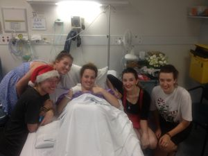 Stephanie Kay surrounded by a team of supporters in hospital.