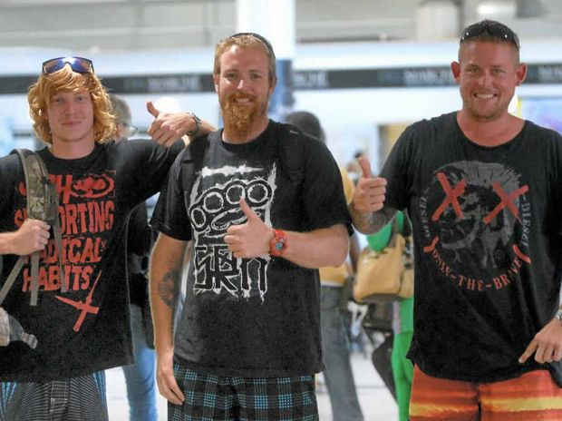Corey Laffin (left), Shane Martin and Brad Heron (right) are all smiles as they return to Mackay after narrowly escaping the wrath of Typhoon Haiyan during a kite surfing trip to the Philippines.