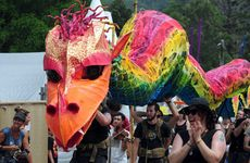 A dragon puppet winds its way along Lamington Drive at Woodford Folk Festival. Photo Seanna Cronin / APN