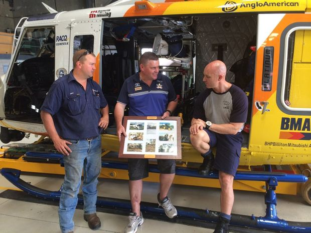 THANKFUL: Matt Trusz (centre) presents a thank you frame to Justin Craib from RACQ CQ Rescue, his boss Greg Keating (left) is also glad to have Matt back at work.