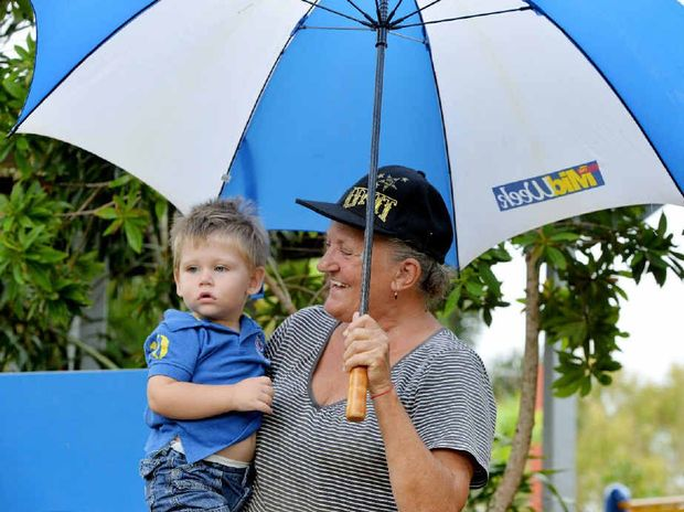 STAY DRY: Grandmother Helen Conway with grandson Lucas Everett, 2, seek shelter from the rain at Iluka Park.