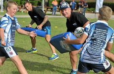 AS GOOD AS IT GETS: NRL legends Alfie Langer (foreground) and Mat Rogers perform tackle drills with a few of the Past Brothers Junior Rugby League Club players.