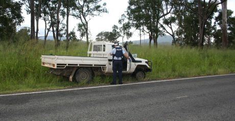 A police officer inspects the stolen vehicle the Rockhampton prison escapees used.