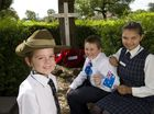 Holy Name Primary School students (from left) Tyson Borey, Cameron Melano and Tremae Jacks in the school's remembrance garden ahead of Anzac Day. Tyson wears an authentic 25th Battalion second world war slouch hat borrowed from the Milne Bay Military Museum.
