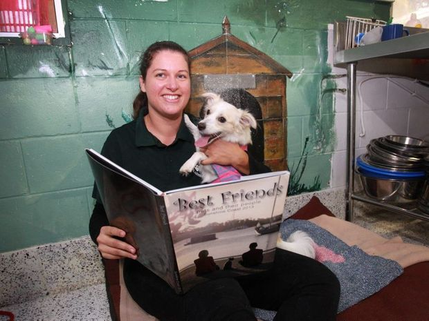 GETTING CLOSE: Sunshine Coast Animal Refuge volunteer Victoria Jenkins reads a book with resident, Squirt.