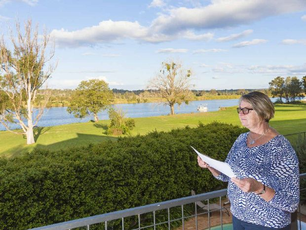 WATER TORTURE: Helen Hearnshaw, on the balcony of her house high above the Grafton levy, is trying to work out how she can avoid a huge insurance increase that would take her annual premiums to almost $10,000.