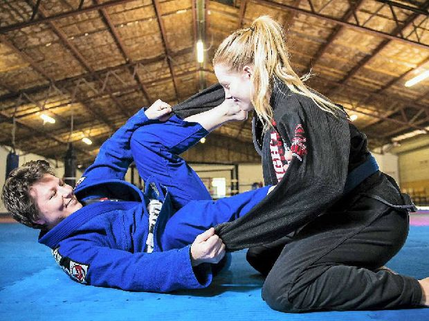 MOTIVATED: Zoe McIntyre (blue) and training partner Kaela Banney at the Gladstone Mixed Martial Arts academy.