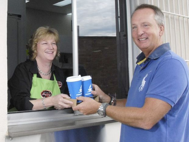 Tracie Batzloff serves customer Marc Leman in the drive-through of Pump 123, soon after its opening in 2011.