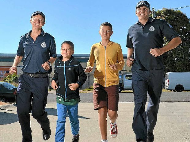 WISH CAME TRUE: Coolum police officer Pierre Senekal will be running for the Make-A-Wish Foundation after his son, Peter,13, (second right) survived liver cancer. Adam Senekal, 9, and officer Blair Doran (right) jog in support.