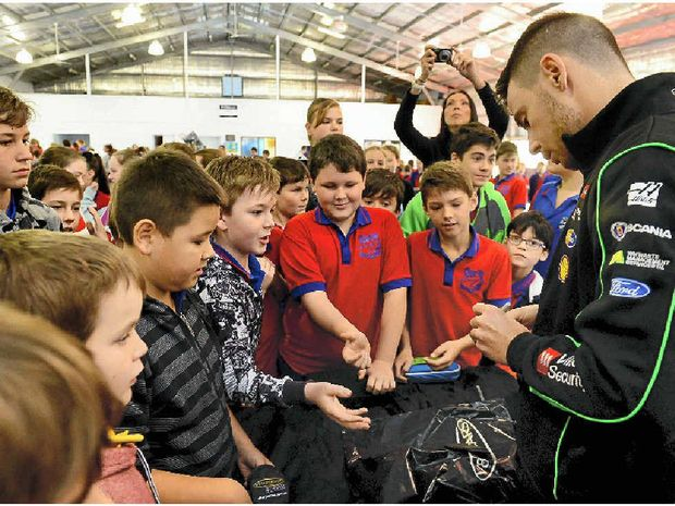 AUTOGRAPH HUNTERS: V8 Supercars star Scott Pye signs items for Karalee State School students.