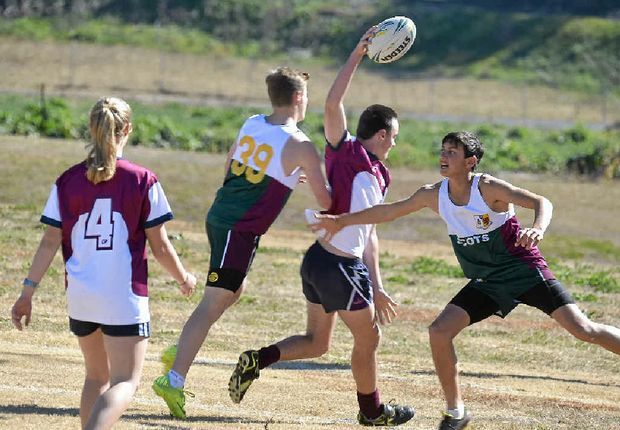 John Butler (Allora State School, with ball) tries to pass two tacklers from The Scots PGC College in touch.