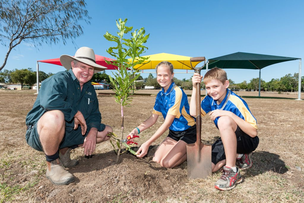 News Bundaberg, 1.8.2014, Kalkie State School, Ray Norris with students Madeline Rehbein & Duncan Allen yr6 plant a Macadamia tree to celebrate 40yrs of production in Australia. Photo Paul Beutel