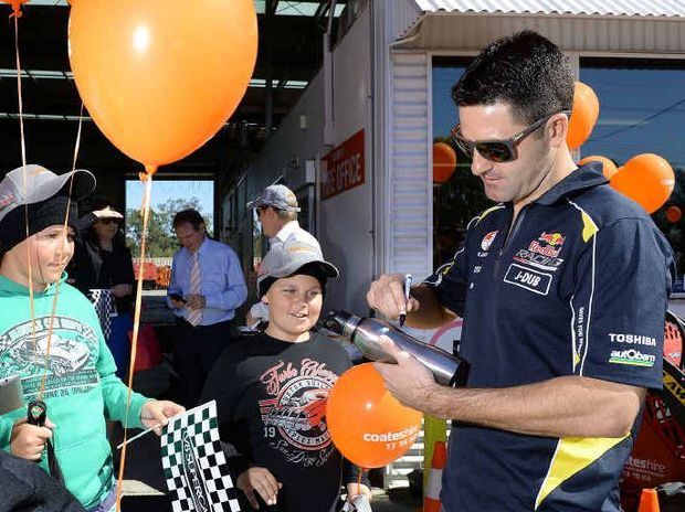 POPULAR DRIVER: Five-time V8 Supercars champion Jamie Whincup signs memorabilia for fans at Ipswich Coates Hire in the lead-up to last weekend's round at Queensland Raceway.