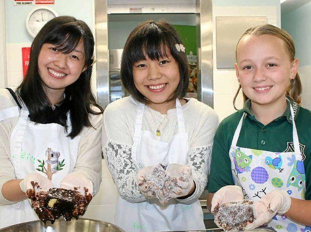 MADE IN AUSTRALIA: Japanese students from Kadina High's sister school in Yamato Takada, Mei Wakabayashi and Aimii Hirabayashi, learn how to make lamingtons with Kadina student Chloe Cassin, 13.