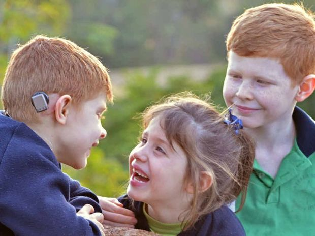 YOU DON'T SAY: Ronan Bell swaps gossip with his proud twin sister Eilish and and brother Rory thanks to a ground-breaking bone-conducting hearing aid.