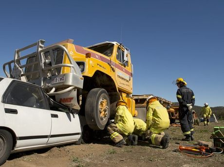 Firefighters prepare to lift a truck from the front of a car during heavy vehicle rescue training.