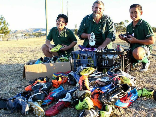 KICK INTO GEAR: Lowood Stags juniors Moses and Isaiah Armstrong-Ravula with club treasurer Nigel Schroeder and the boots to be taken to Fiji this week.
