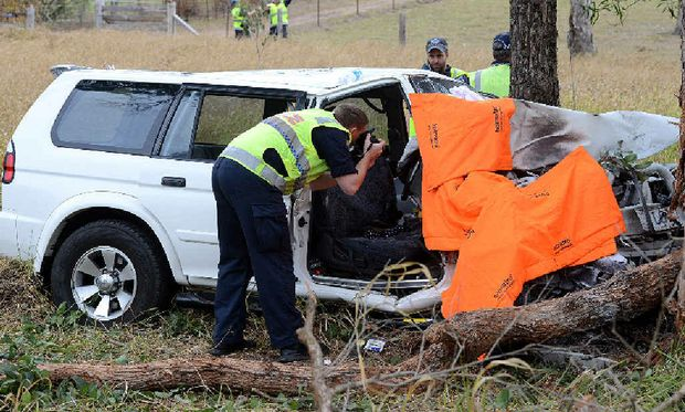 FATAL CRASH: A police investigator at the scene of a fatal traffic crash on the Bruce Hwy at Kybong, after the driver, a Cooloola Cove woman, was cut out of the vehicle and, below, paramedics work behind screens to save the woman (left).