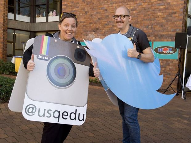 Being social through different medias are Samara Hoffman and Jeremy Tibballs at USQ Open Day.