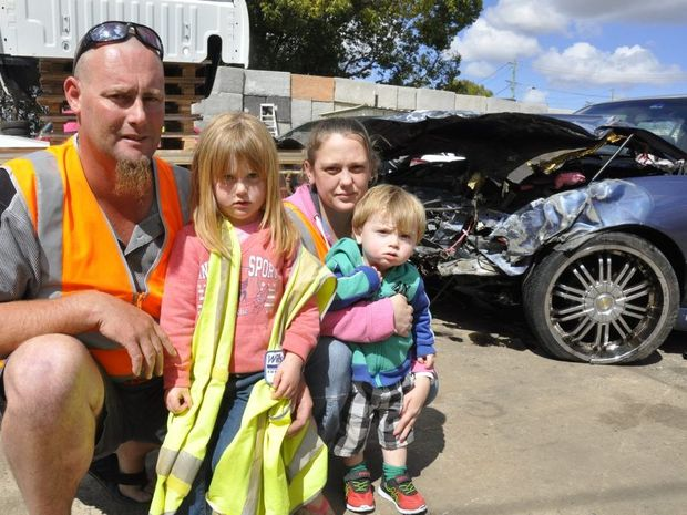 Oakey couple Wes Whitbread and Melissa Ambrose and their children (from left) Dakota and Aston Whitbread inspect crash damage to their family car.