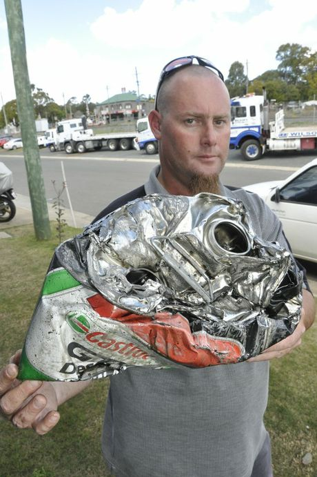 Oakey man Wes Whitbread inspects a 20L oil drum which was struck by his car before it crashed into an oncoming ute on the Warrego Hwy near Oakey.