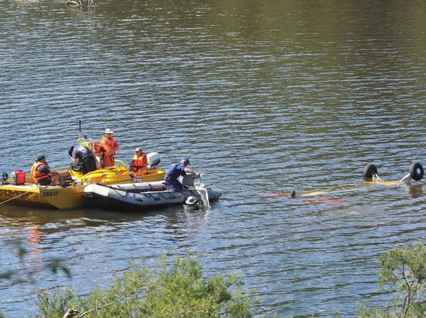 SES and Police divers pictured in April trying to retrieve the plane that crashed into the Clarence River at Yates Crossing, Ewingar.