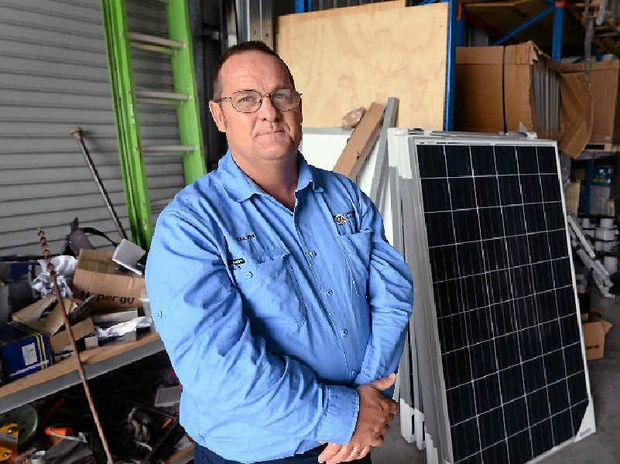 SOLAR CUTS: Climate Care Electrical owner Kelvin Rasmussen is worried about the effects that local businesses could face if the Federal Government drops the Renewable Energy Target. (INSET) An aerial view of homes in Rockhampton with solar panels.