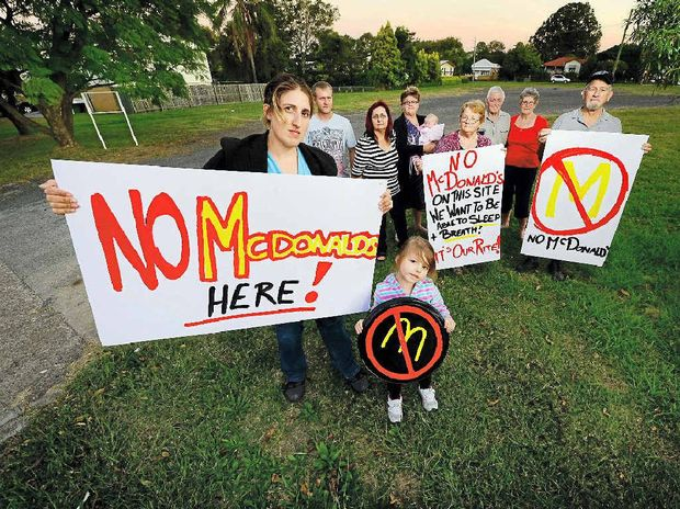 GOOD RESULT: Raceview residents (from left) Jessica McLean, Ariana McLean, 4, Dion McLean, Silvia Wells, Kaye Petie, Sylena McLean, nine weeks, Jeannine and Barry Sippel (front), and Kay and Kevin Ardrey (rear), protest against a proposal to build a McDonald's restaurant at Raceview.